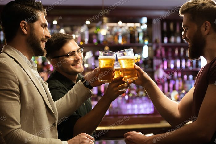 Cheerful young men toasting with beer