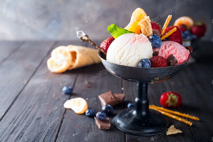 Homemade Organic Vanilla Ice Cream with Mint and ice berries on wooden background
