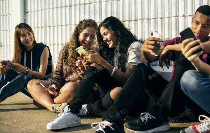 Gruppe junger Teenager-Freunde, die zusammen mit dem Smartphone-Social-Media-Konzept chillen