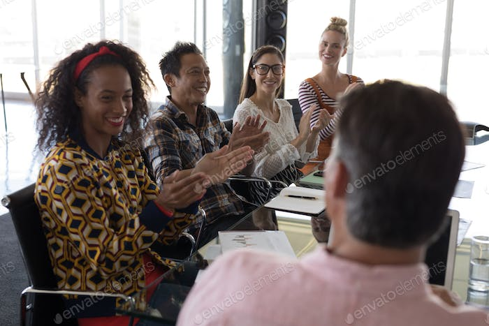 Side view of young multi-ethnic business colleagues applauding businessman in modern office