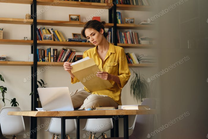 Beautiful woman in shirt sitting on desk with documents thoughtfully working in modern office