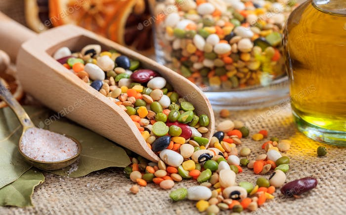 Wooden scoop and mixed raw legumes