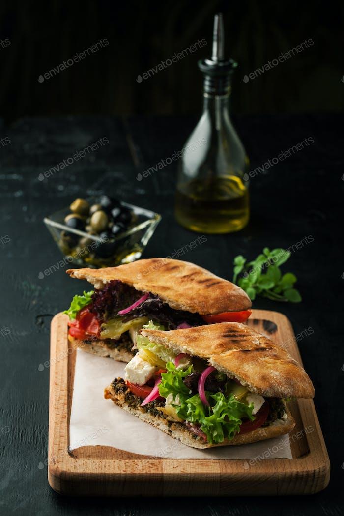 Leckeres Sandwich mit Gemüse, Oliven und Pesto
