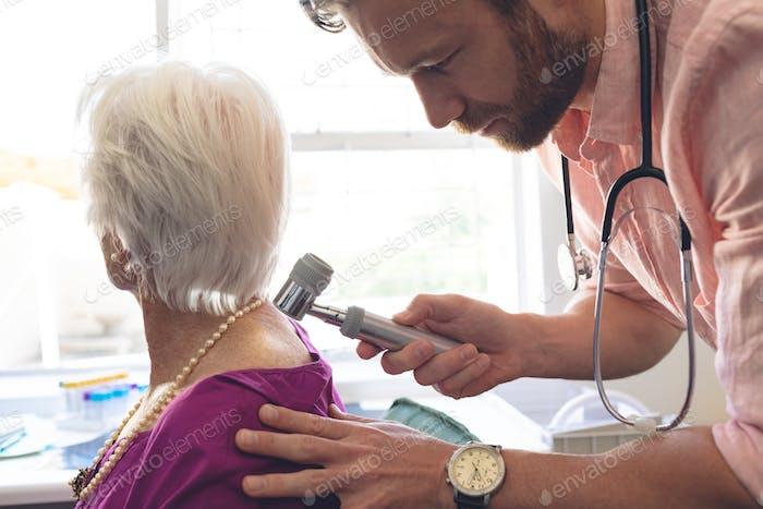 Seitenansicht des kaukasischen männlichen Dermatologen untersucht ältere Patienten durch Dermatoskopie