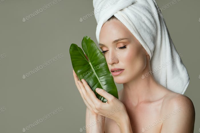 A Beautiful Girl With A Towel On Her Head Holds A Green Leaf In Her Hands. Cleanliness And Care.