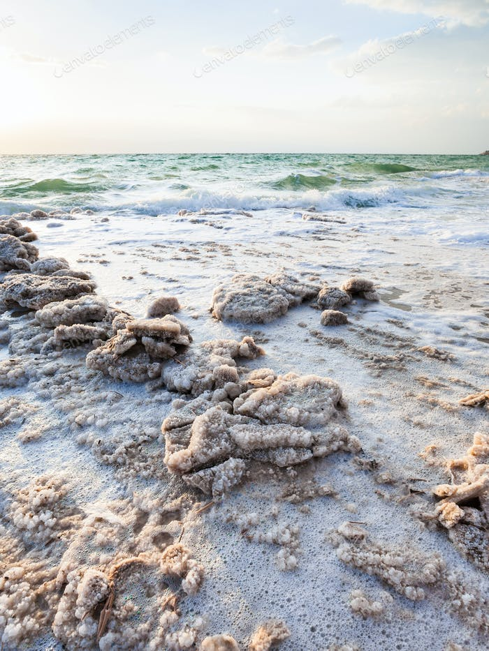 crystals of salt on coast of Dead Sea in evening