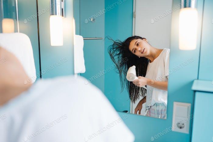 Porträt der jungen Frau mit Haartrockner im Badezimmer