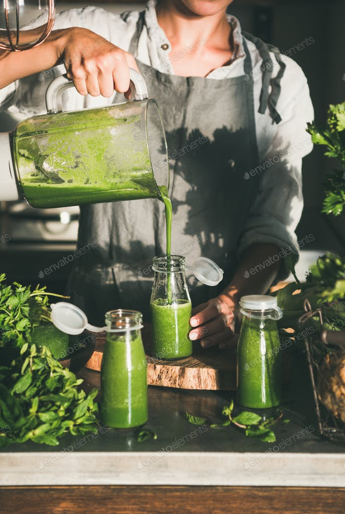 Young female pouring green smoothie from blender to bottle