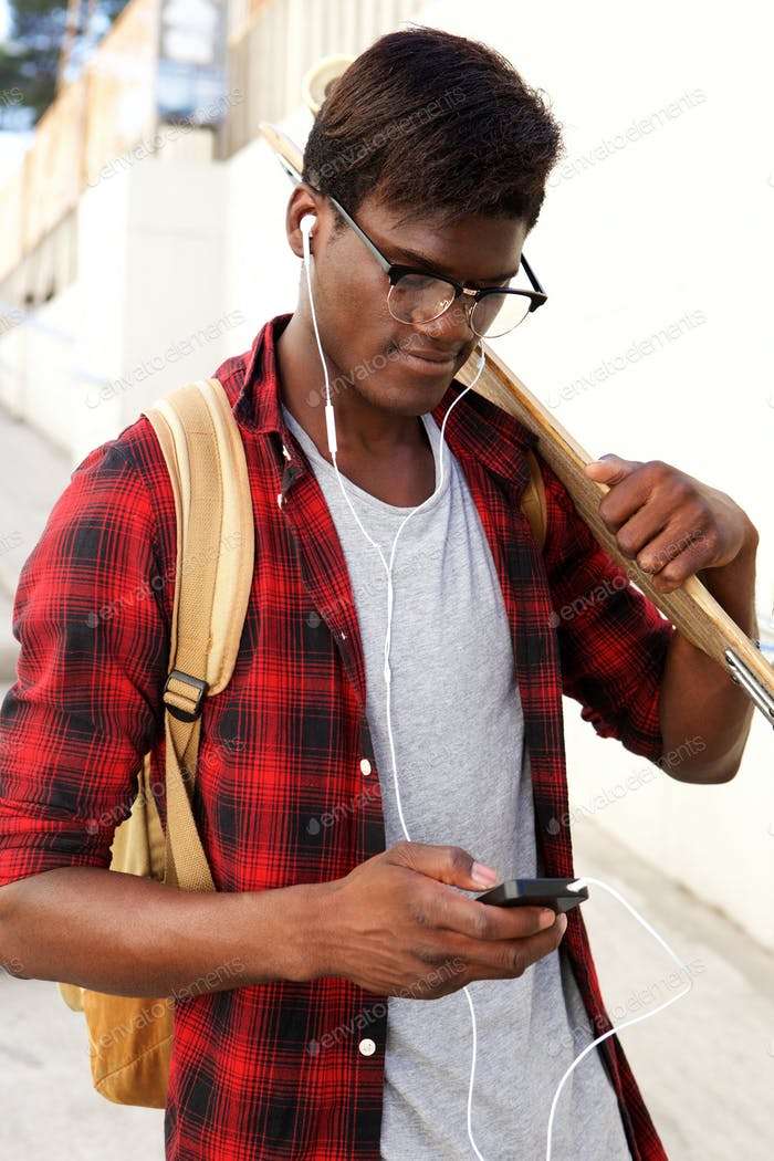 young african man with skateboard looking at mobile phone