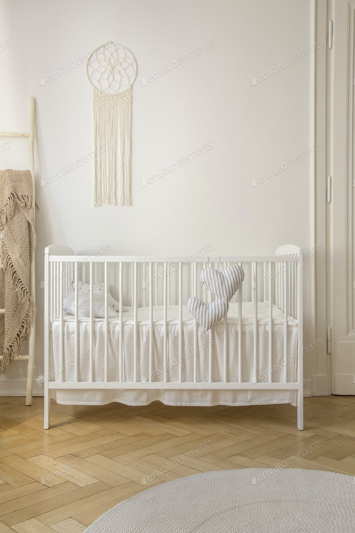 Two heart shaped pillows placed on baby crib standing in white r