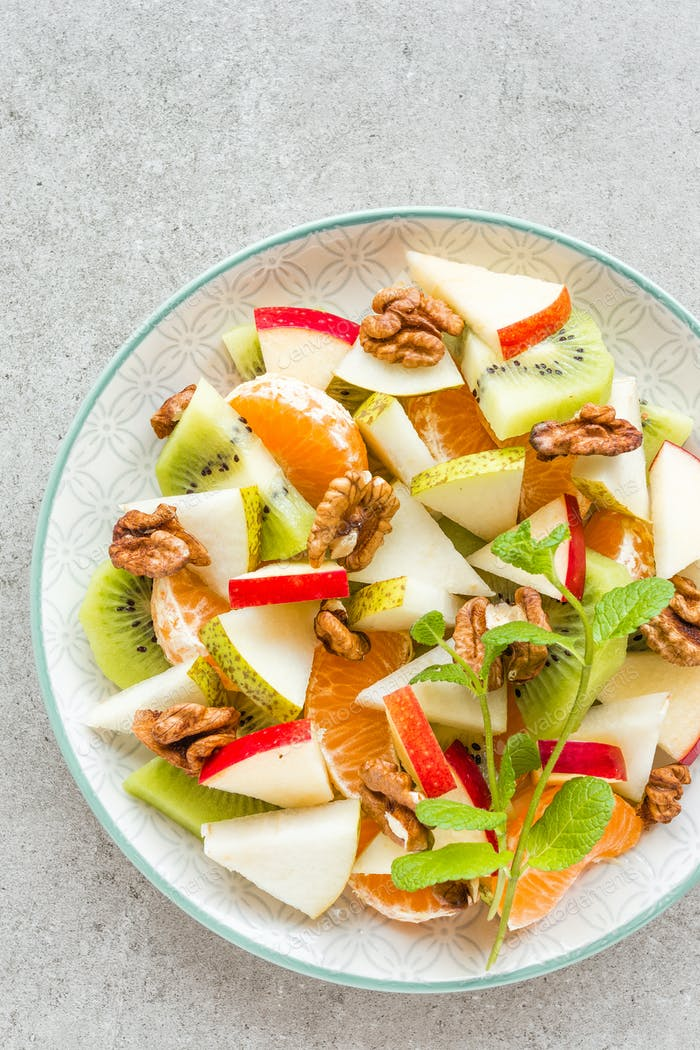 Fruit salad of fresh sweet apple, pear, tangerine and walnuts. Healthy vegetarian food