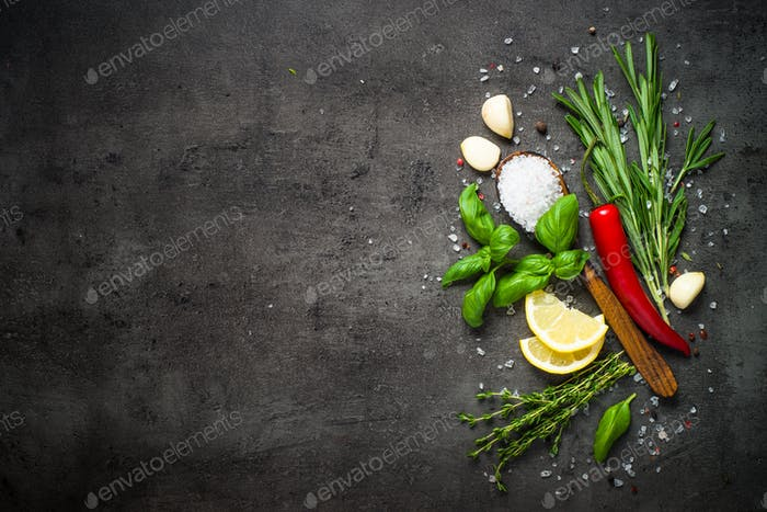 Selection of spices and herbs on dark stone table