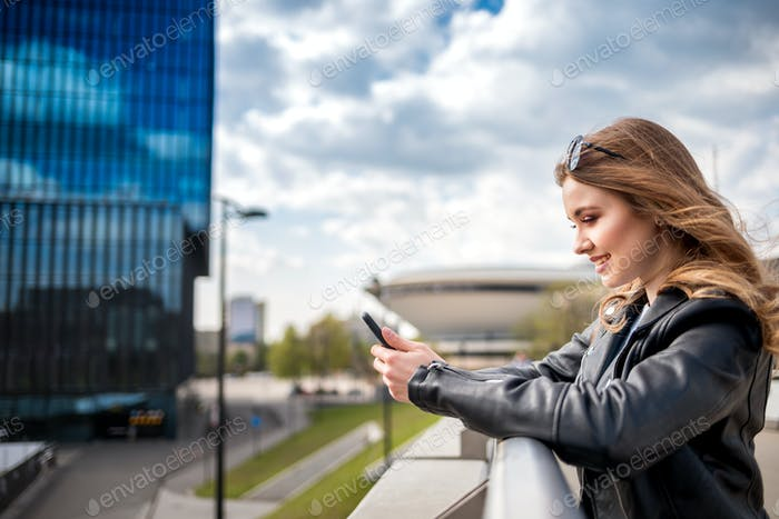 Successful young businesswoman typing on phone among modern office buildings in big city