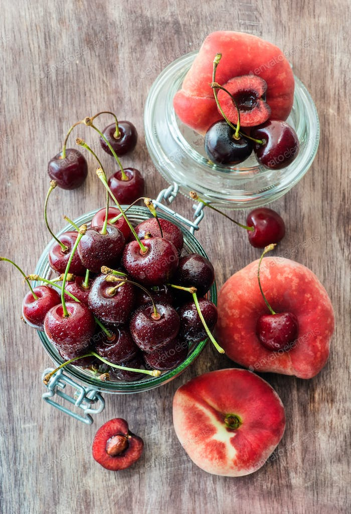 Cherries and donut peaches over wooden background
