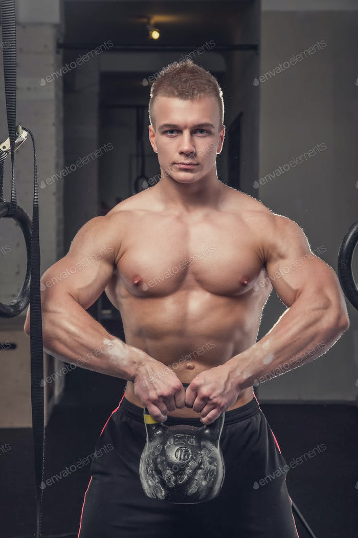 Bodybuilder holds lifting weight in a gym club.