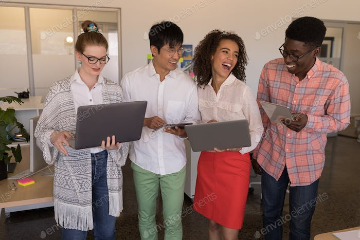 young happy diverse business colleagues using laptop and digital tablet in modern office