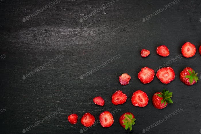 Sliced strawberries with leaves on black backfround. Top view, frame. Copy space. Summer fruit