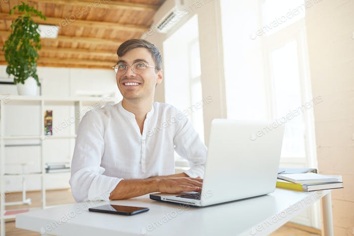 smiling young businessman wears white shirt and glasses feels happy