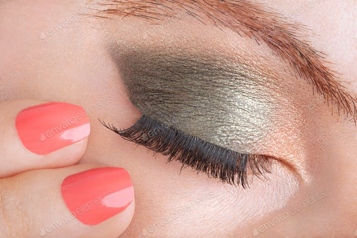 Frau mit grünem Auge Smokey Make-up und Korallen Nagellack