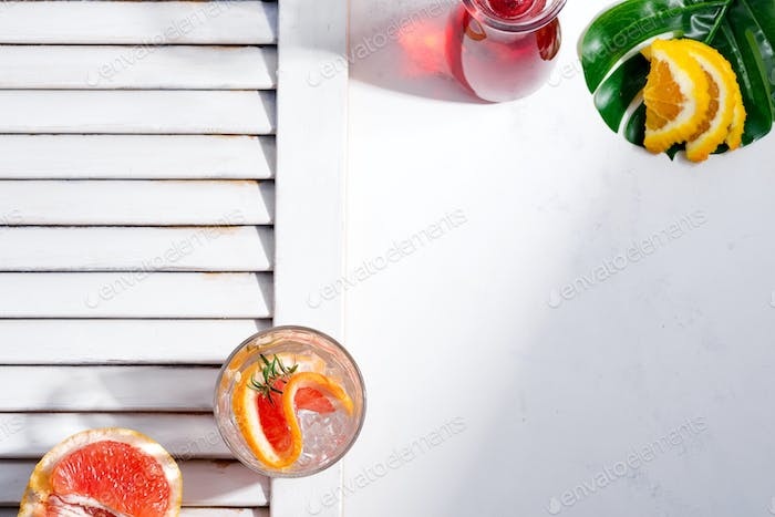Cold summer drink in a glass with slice of grapefruit and ice cubes on a white background with part