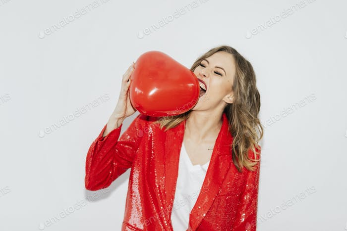 Woman in a red jacket biting a red balloon