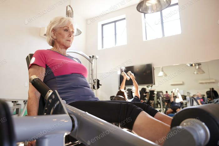 Active Senior Woman Exercising On Equipment In Gym