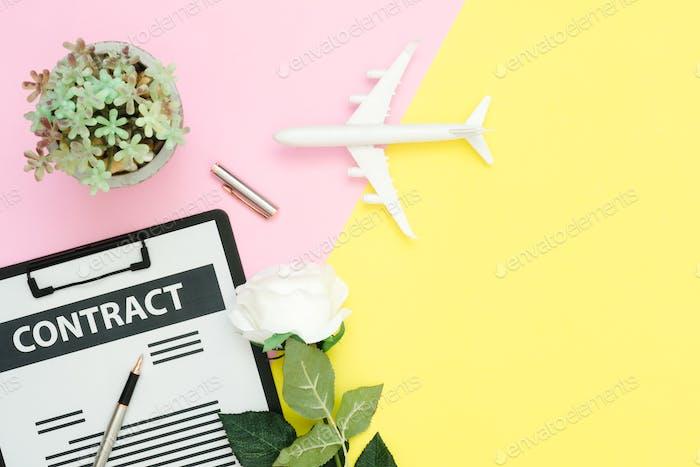 Draufsicht Layout von Vertragsdokument, Flugzeug und TuscheStift mit weißer Rose und Baum.