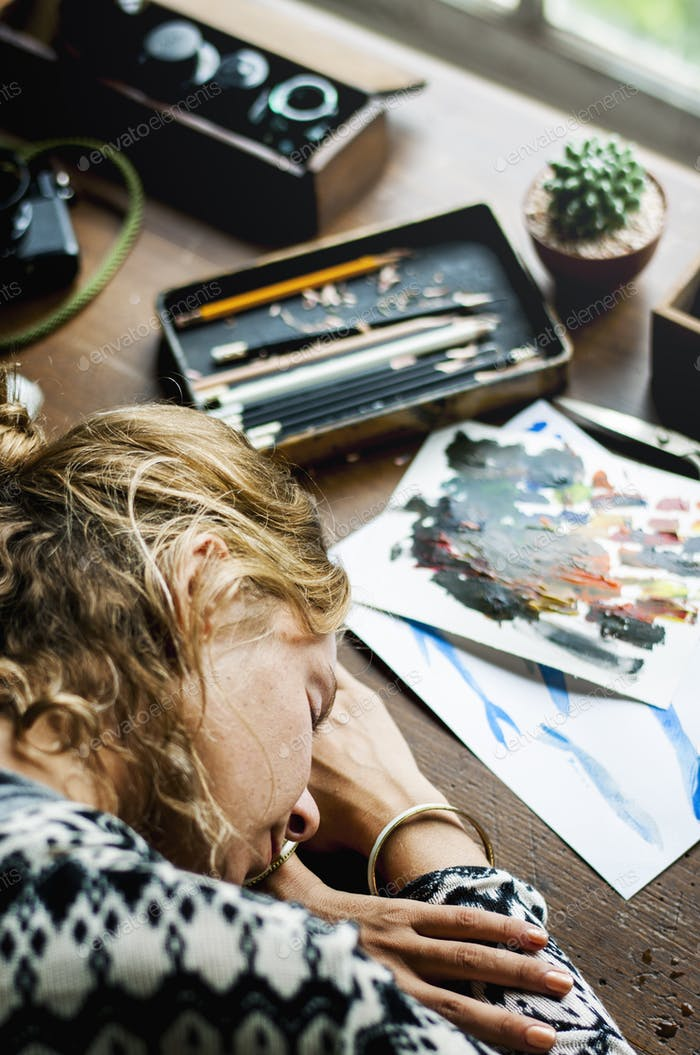 Closeup of artist woman taking a nap on work table