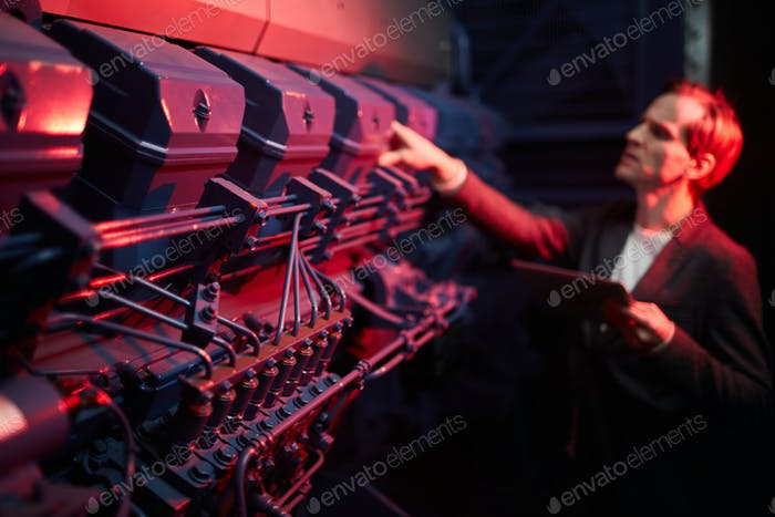 Maintenance engineer examining backup generator