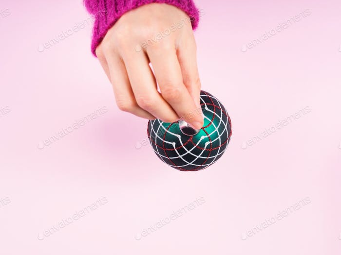Woman's hand holding christmas bauble
