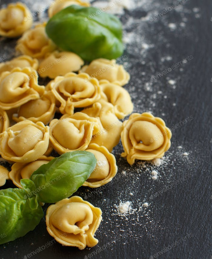 Homemade raw Italian tortellini and basil