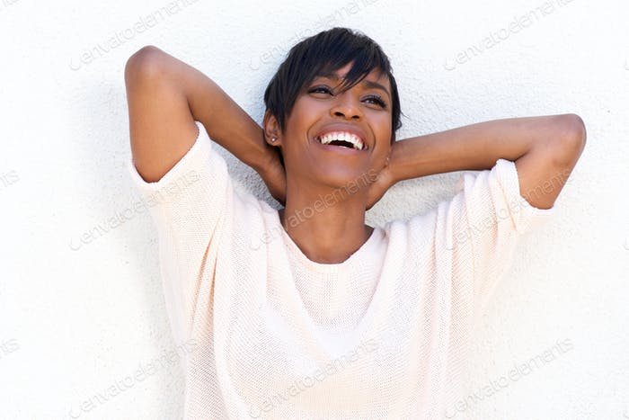 Close up cheerful young lady with hands behind head on white background