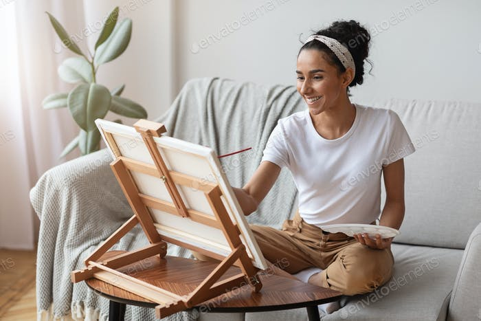 Woman with easel and palette painting at home