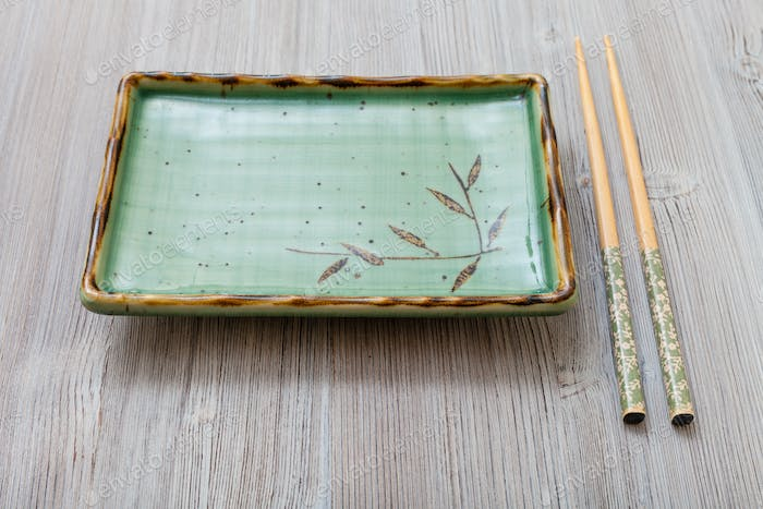 one green square plate and chopsticks on gray