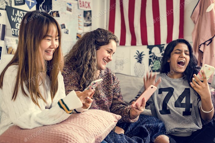 Teenage girls using smartphones in a bedroom internet in slumber party