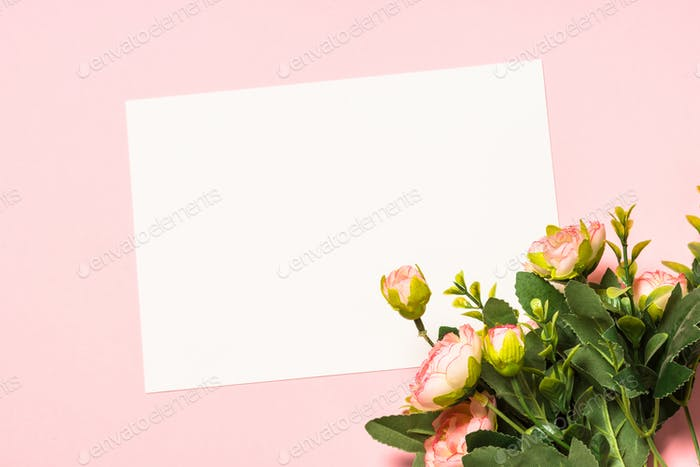 Empty paper sheet and flowers on a purple background