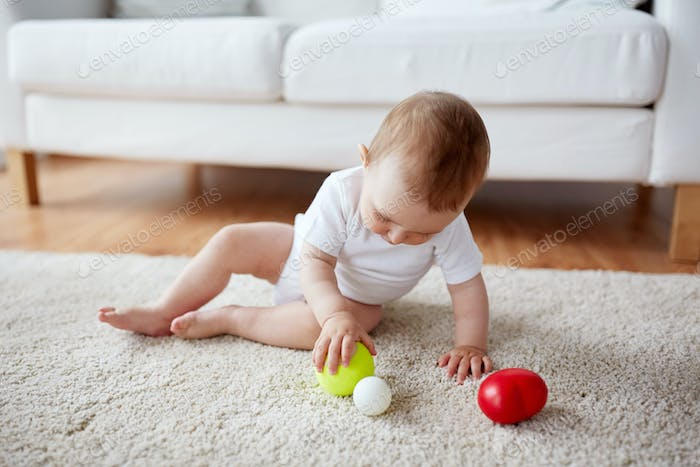 happy baby playing with balls on floor at home
