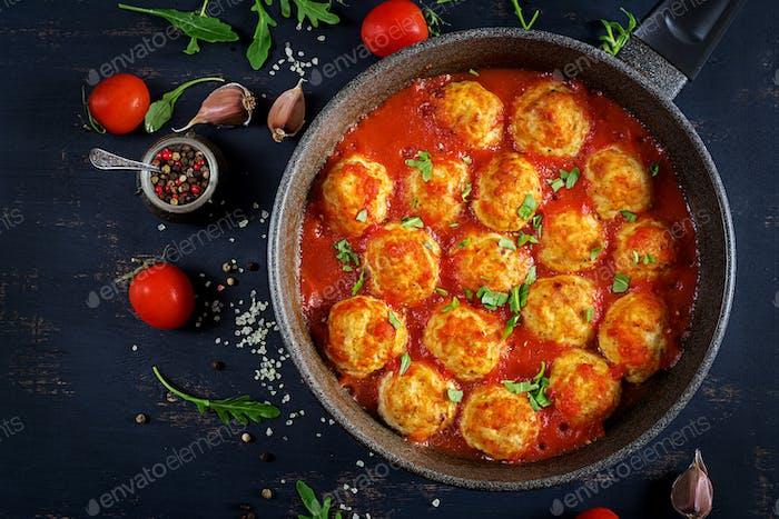 Hähnchenfleischbällchen mit Tomatensauce in einer Pfanne. Abendessen. Draufsicht. Dunkler Hintergrund.