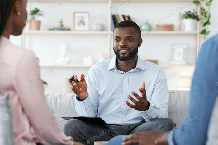 Marital Therapy. Black man professional psychologist consulting married couple at his office