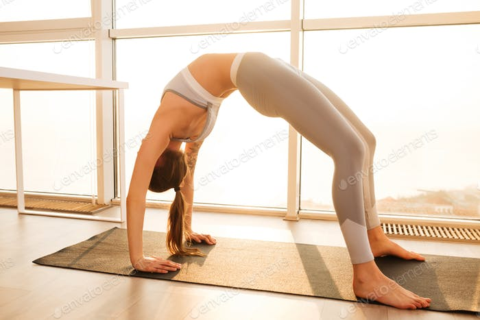 Pretty girl standing in bridge exercise while practicing yoga poses on yoga mat at home