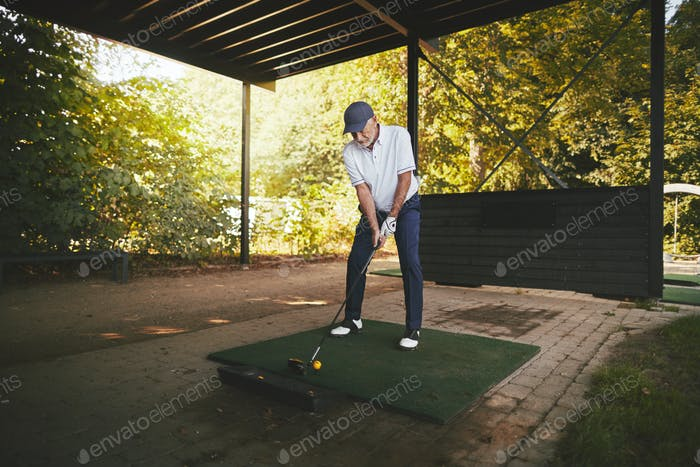 Sporty senior man practicing golf at a driving range