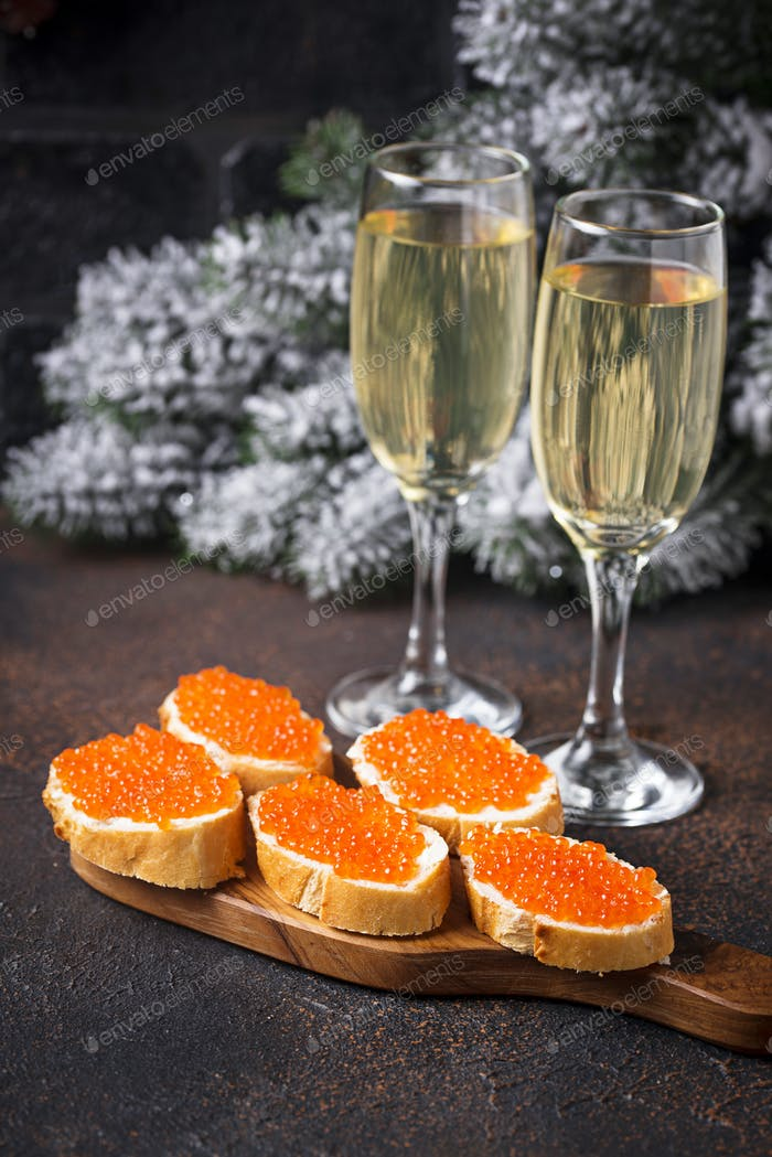 Toasts with red salmon caviar and champagne
