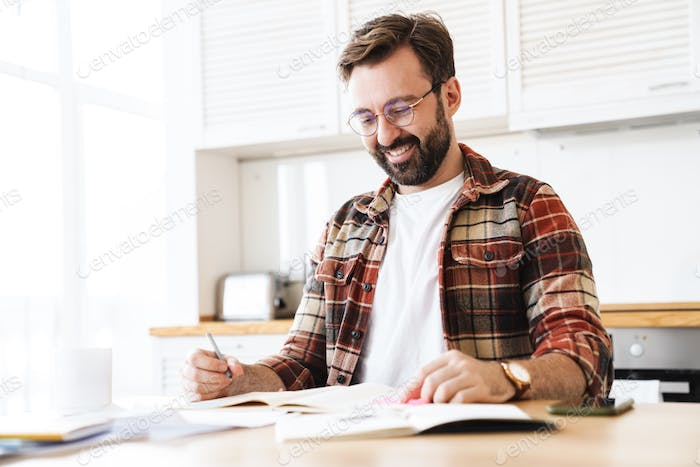 Portrait of excited bearded man smiling while working at home
