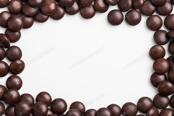 Frame of brown chocolate candy on white background with space