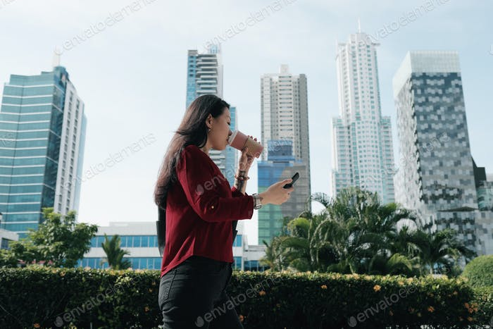 Thumbnail for Chinese Woman With Phone Walking And Drinking Coffee