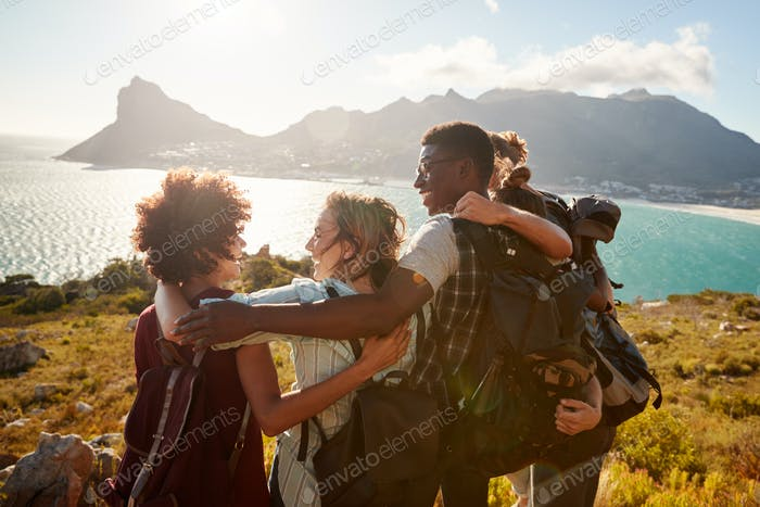 Millennial friends on a hiking trip embrace at the summit to celebrate their climb, back view