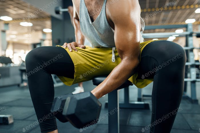 Muscular man doing exercise with heavy dumbbell
