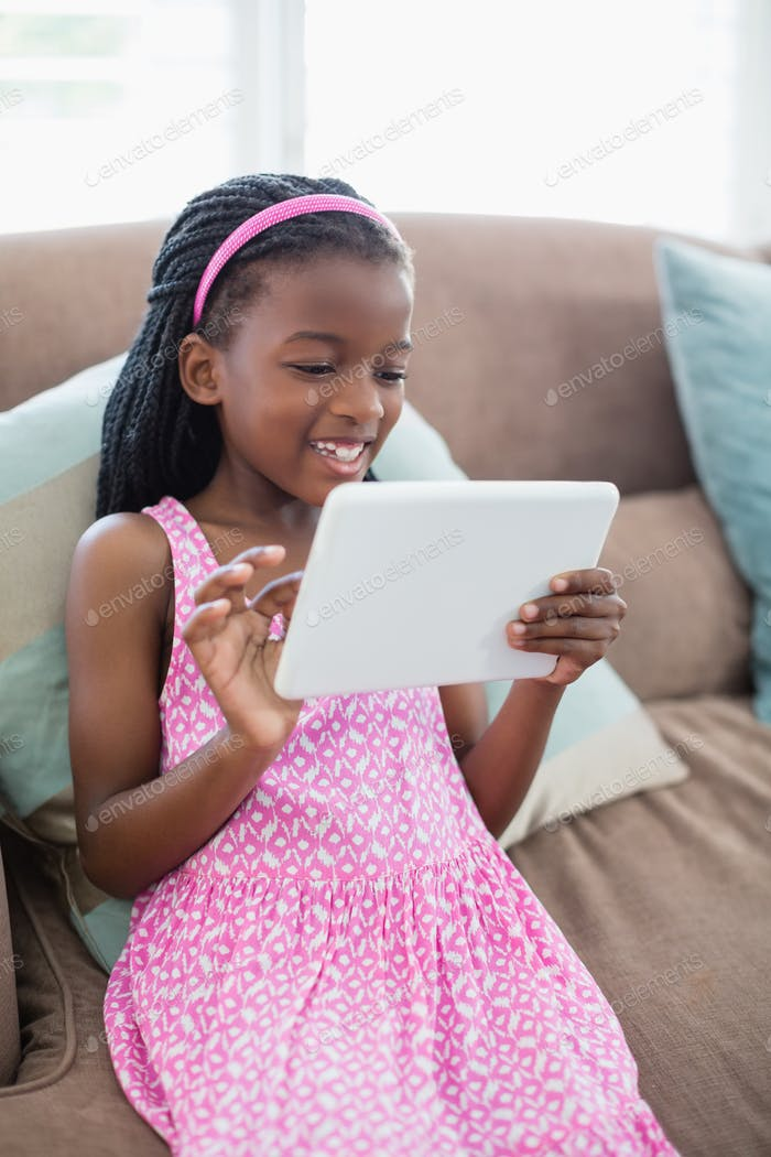 Mädchen sitzen auf dem Sofa und mit digitalem Tablet im Wohnzimmer