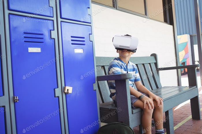 Boy using virtual reality glasses while sitting on bench by lockers