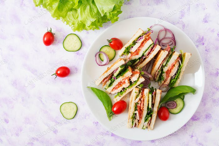 Club sandwich with chicken breast, bacon, tomato, cucumber and herbs. Top view